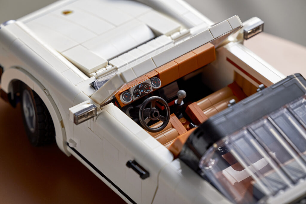 A close up shot of the interior of the new LEGO Porsche set 10295 featuring gear shifter, handbrake, and working steering wheel