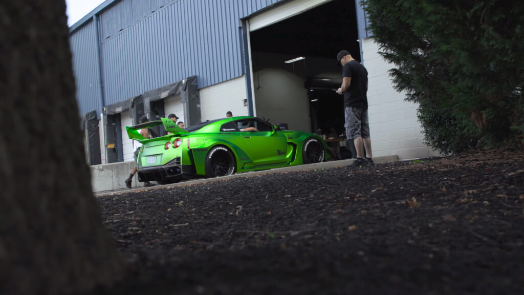 Green Nissan GT-R with Liberty Walk wide body kit as seen at the 2021 Tuner Evolution show in Philadelphia