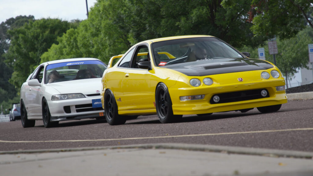 Yellow DC2 Acura Integra Type R followed by a white Acura Integra Type R with JDM front end as seen at the 2021 Tuner Evolution show in Philadelphia